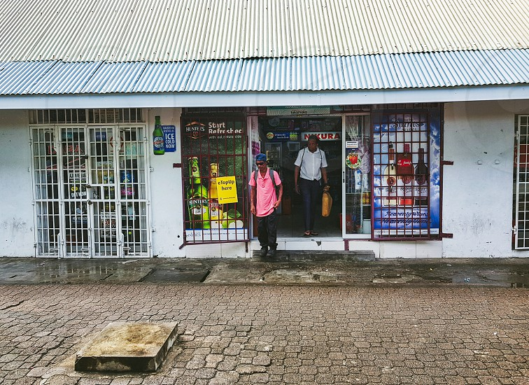 People exiting a small neighborhood store. photo