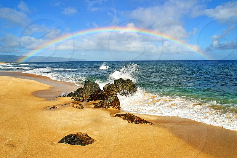 A rainbow over Rock Piles Beach on the North Shore Oahu Hawaii. photo