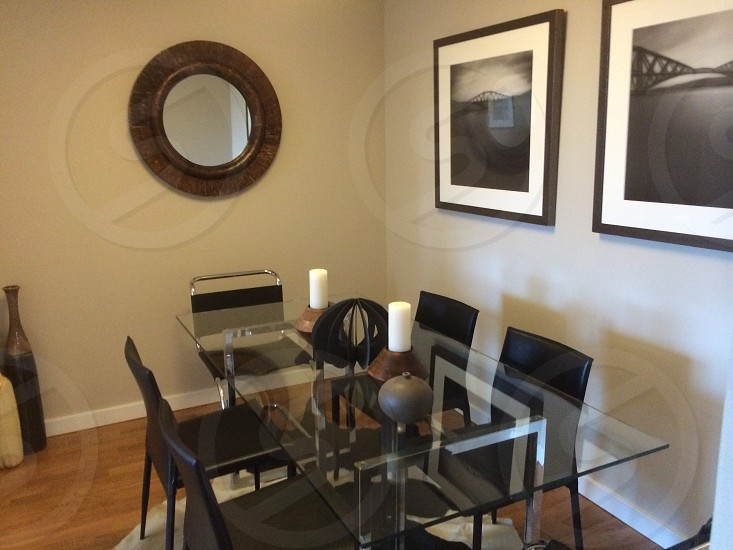 rectangular clear glass dining table and black leather chairs beside white wooden wall with grayscale photography of bridges photo