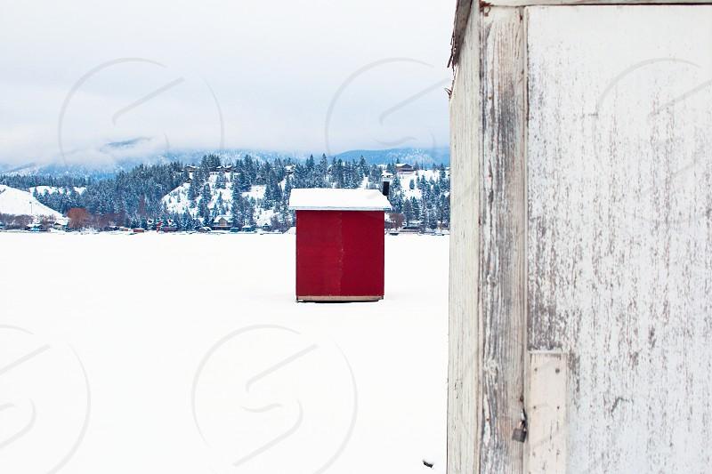 winter ice fishing ice hut red shack snow frozen lake mountains photo