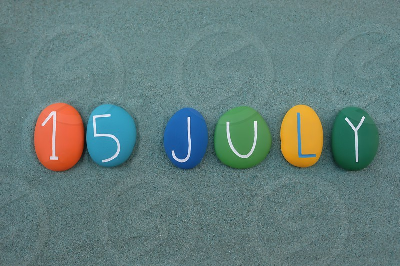 15 July calendar date composed with multi colored stones over green sand photo