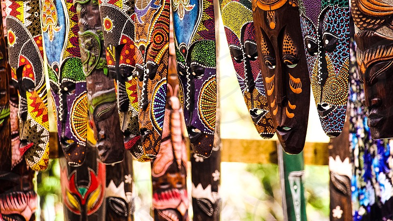 orange brown and blue tribal masks hanging on wall photo