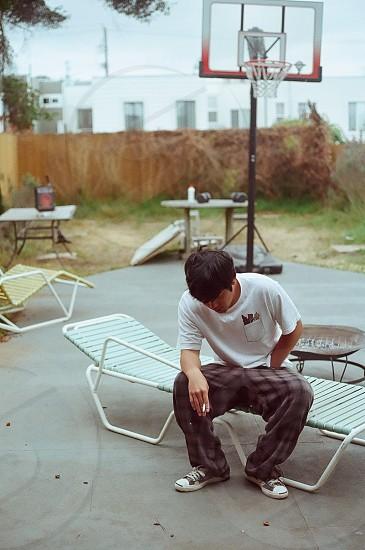 man in white shirt sitting on white beach chair photo