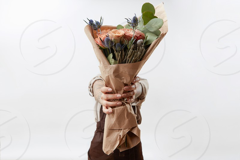 Delicate flowers living coral roses and eryngium as a beautiful bouquet in girl's hands on a gray background. Place for text. Congratulation card for Woman's or Mother's Day. photo