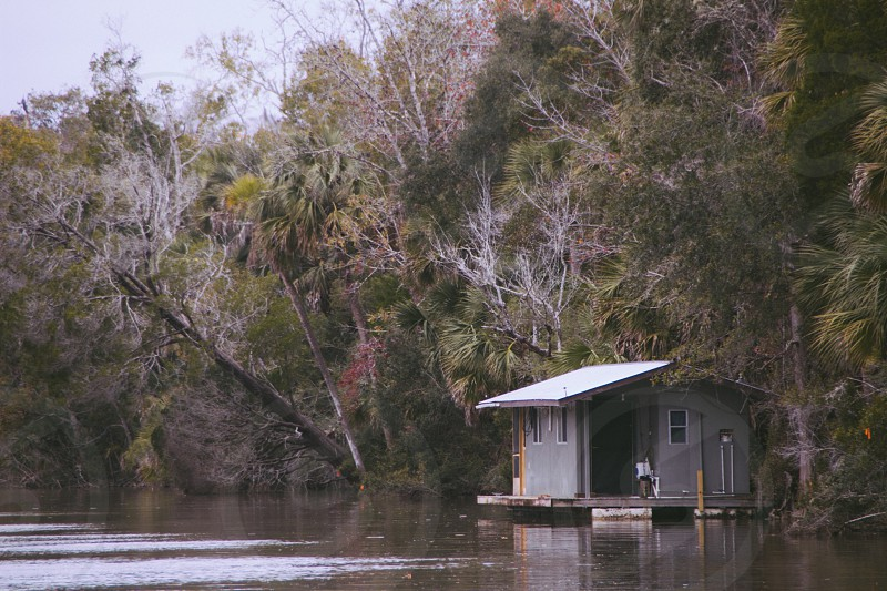 floating gray wooden house beside the river photo