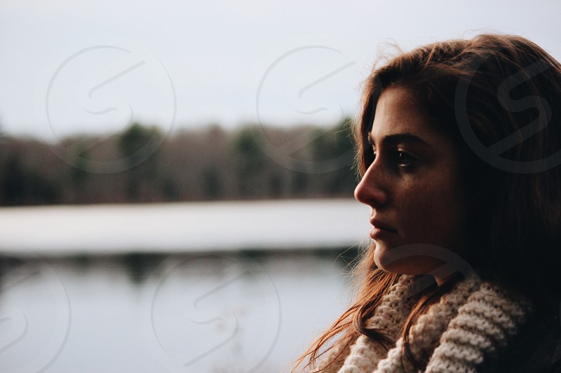woman wearing white knitted scarf looking forward in shallow focus lens photo