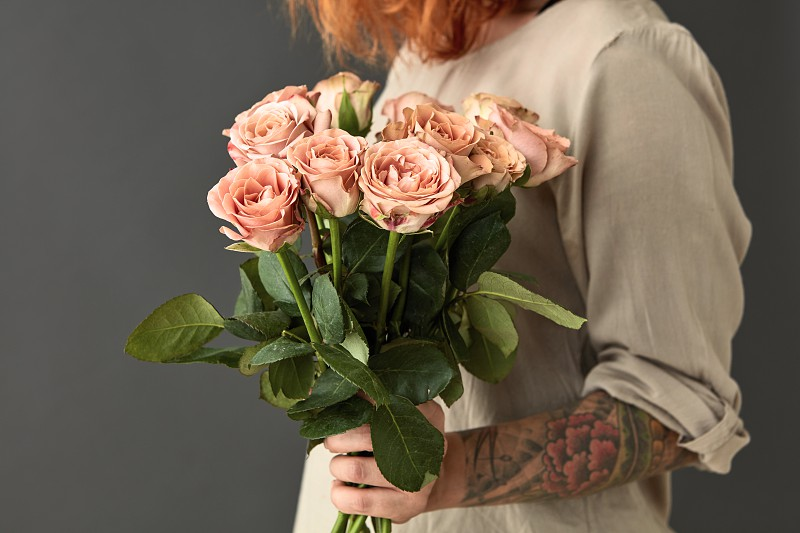 Girl with a tattoo holds a bouquet of fresh pink roses on a gray background. Happy valentine's day. Happy Mother's Day photo