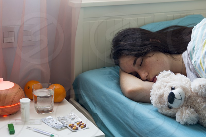 The young girl has a cold lies in bed at home feels unwell takes medicines and vitamins sleeps with a toy bear. photo