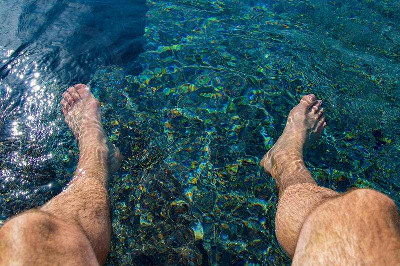 Point of view with feet in the pool water.  photo