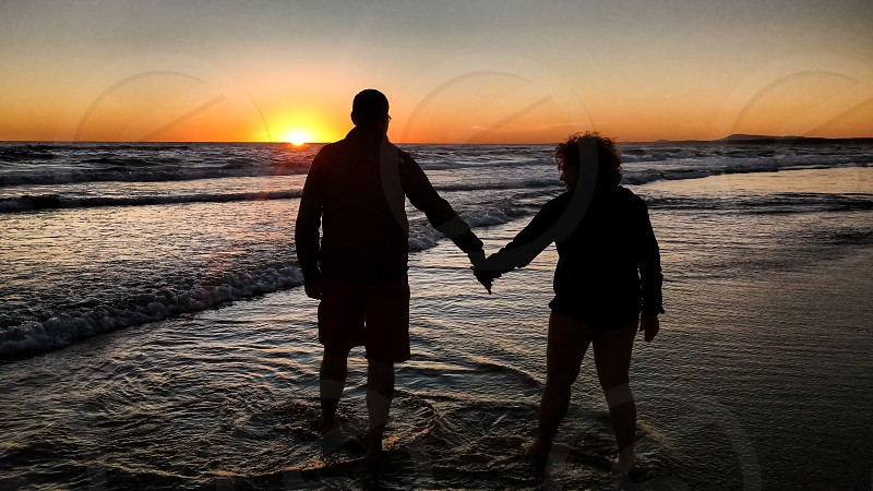 an old couple enjoying a lovely sunset at the beach photo
