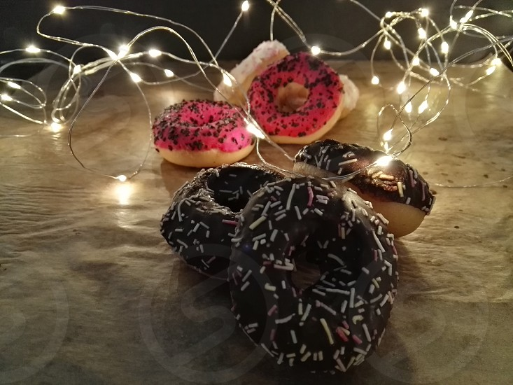 sweet donuts on rustic background with christmas lights photo