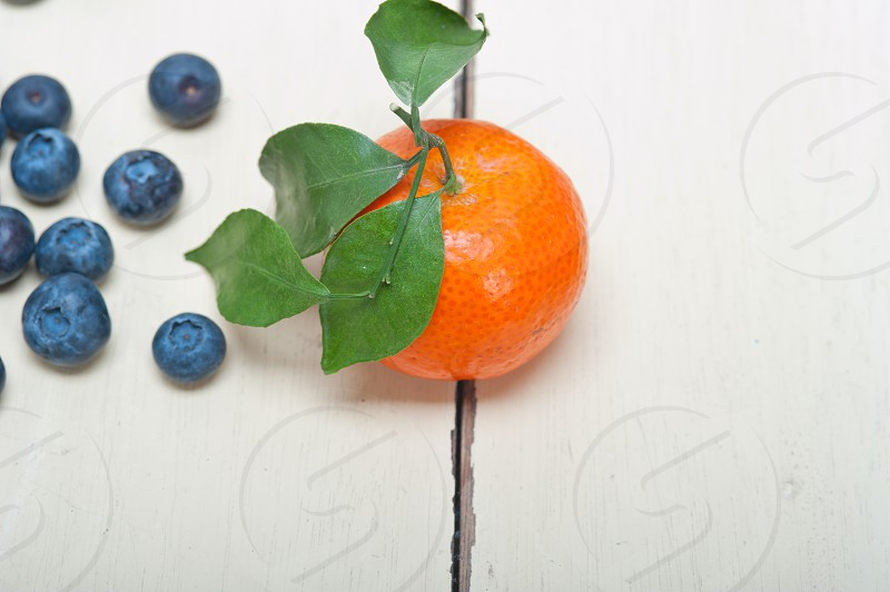 tangerine and blueberry on white rustic wood table photo