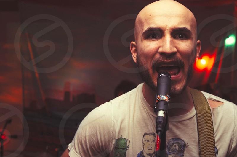 singing man in white crew-neck shirt using black microphone photo