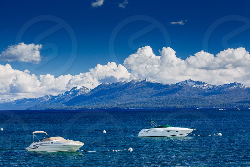 Lake Tahoe boating summer snow on mountains photo