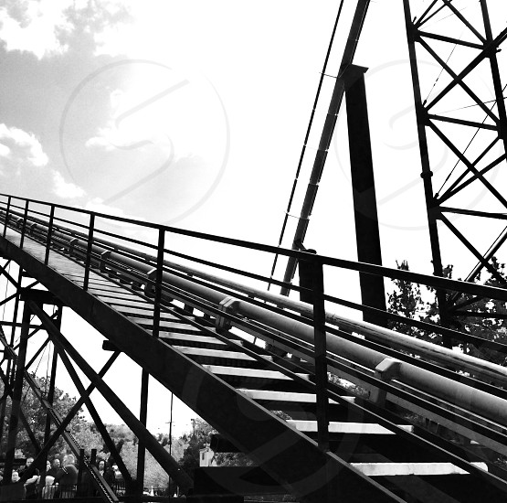 grayscale photo of roller coaster track photo