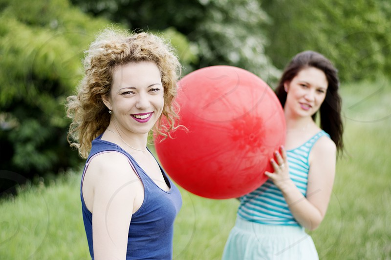 One girl is holding big red balloon and singing while other looking straight to camera photo