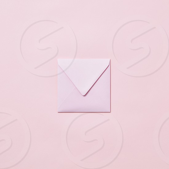 Empty handmade envelope for congratulation card on a light pink background with copy space. Mockup. photo