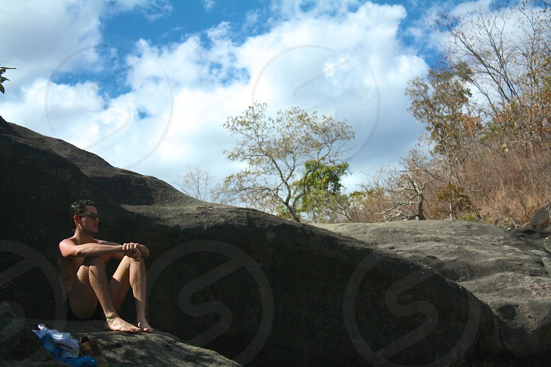 man wearing black framed sunglasses sitting on gray stone photo