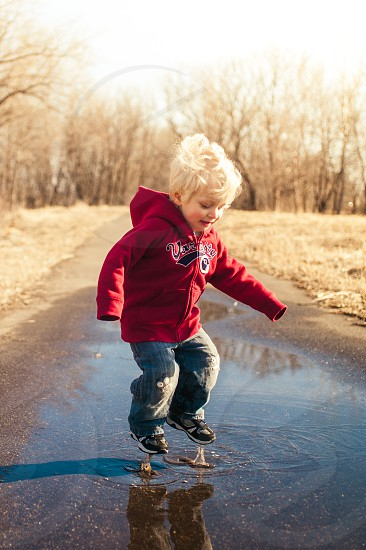 A young boy having fun jumping in puddles outside. photo