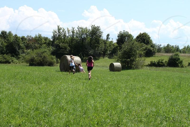 Children having fun pushing a round hay bale photo