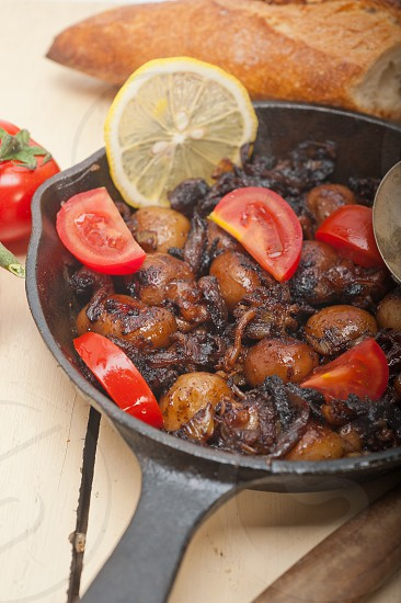Baby cuttle fish roasted on iron skillet with tomatoes and onions over rustic wood table photo