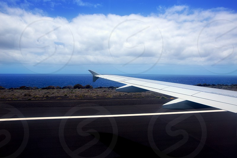 Airplane landing in canary Islands with black volcanic soil and Atlantic ocean photo