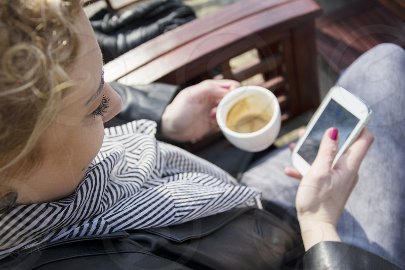 Young girl drinking coffee at bar and looking at her mobile phone photo