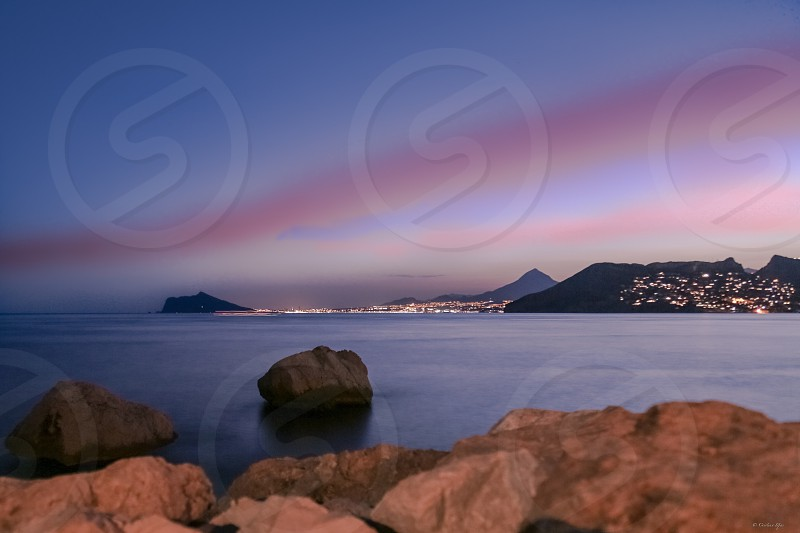 long shot photography of body of water with rocks surrounded by buildings over the purple atmospheric optics photo