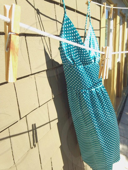 teal and white polka-dot cami-strapped surplice dress hanging on clothes airer during daytime photo