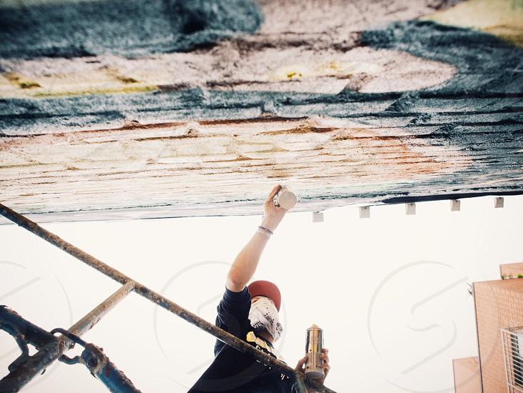 man wearing white mask using spray paint photo