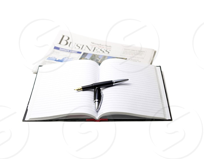 newspaper pen and notebook on white background photo