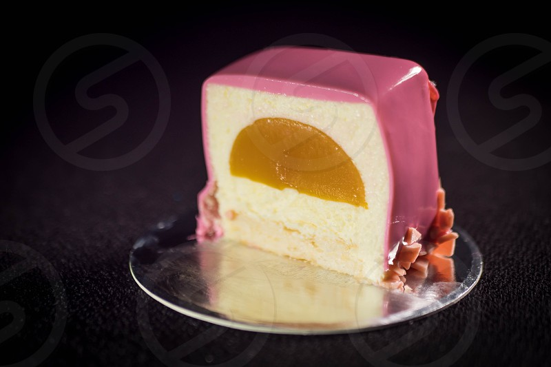 Contemporary Cake covered with pink mirror glaze and in a section with mango slice inside on dark background. photo