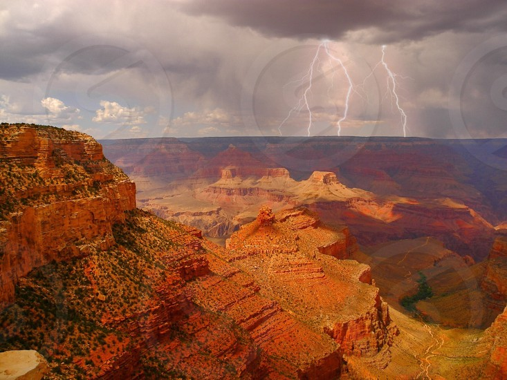 grand canyon with lightning strikes during daytime photo