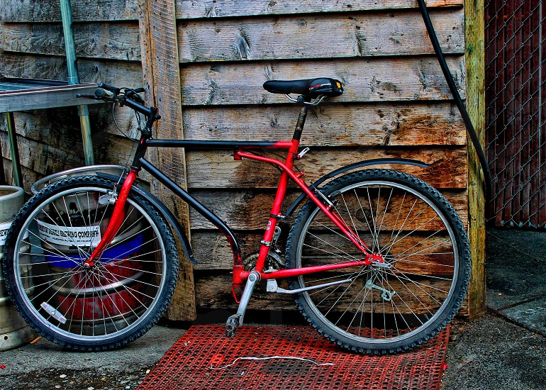 A red bicycle is parked near the wall of a  weathered rustic house photo