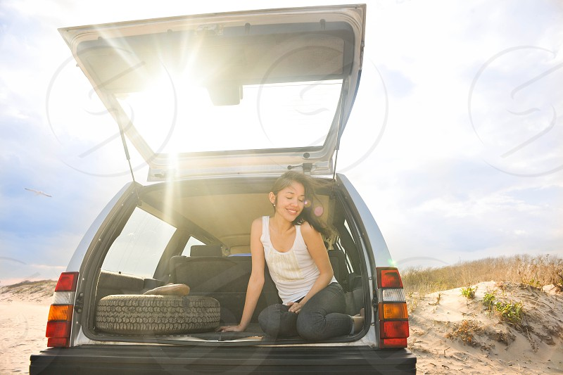 woman wearing white tank top sitting at the back of the passenger vehicle photo