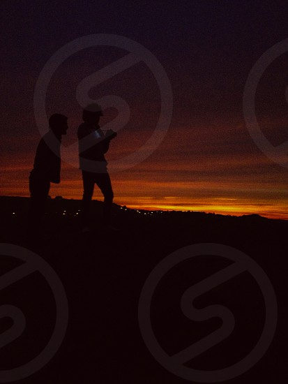 silhouette of two person over golden hour photo