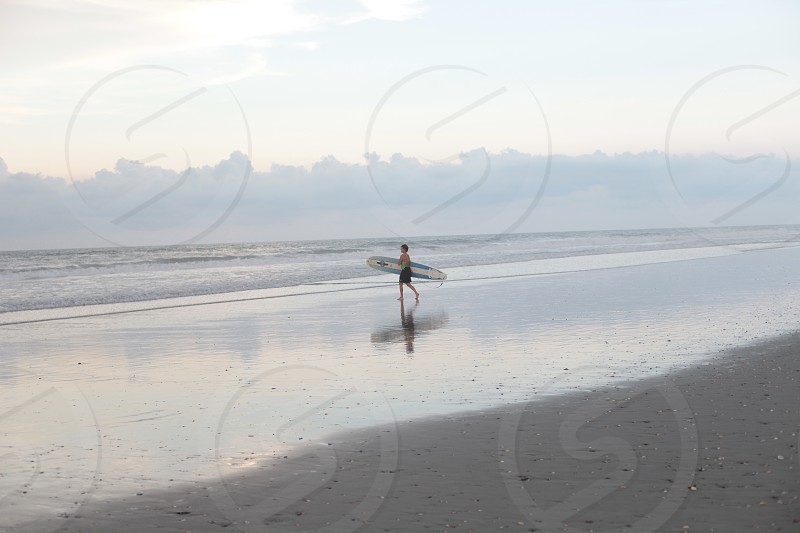 surfer with surfboard walking towards the beach under grey cloudy sky photo