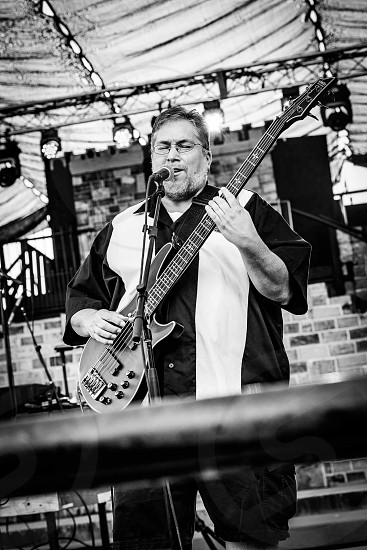 grayscale photography of a man playing bass guitar on an concert even singing a song photo