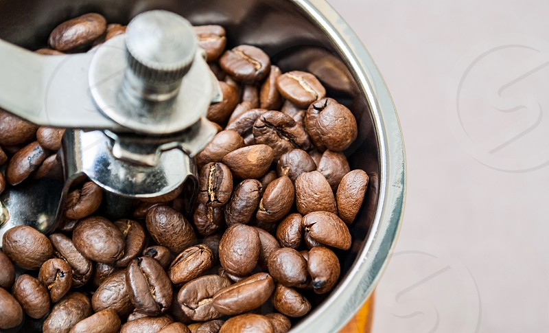 Roasted coffee beans in a manual coffee grinder. Close-up shot.Morning routine. photo