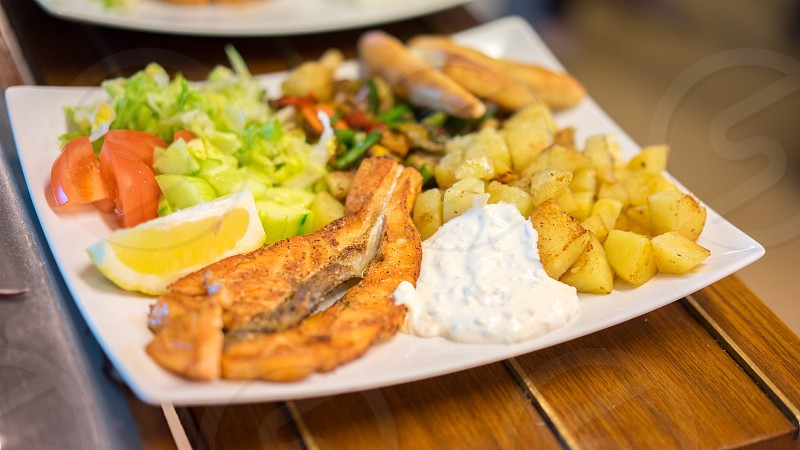 fried fish potatoes sliced tomatoes on plate photo