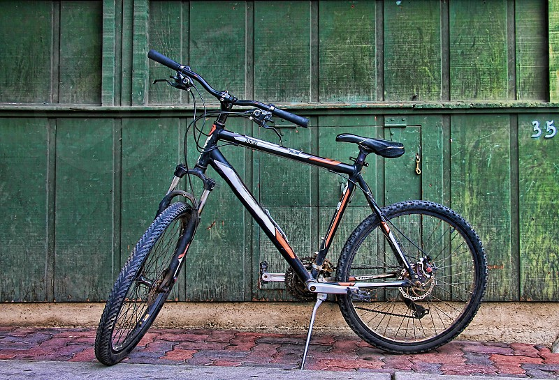 Retro bicycle parked near a weathered wooden green wall. photo