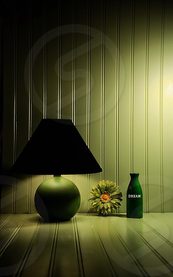 "Green bedside lamp with a flower and green vase with the word ""dream"". photo"
