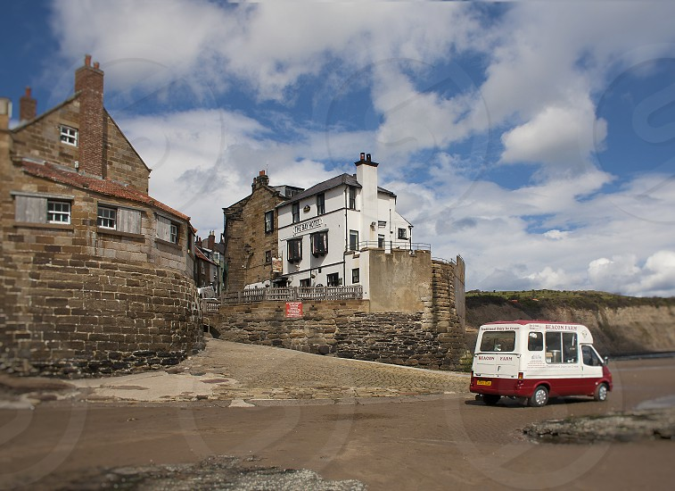 England English Seaside Village with classic vingtage Ice Cream Truck on the beach. photo
