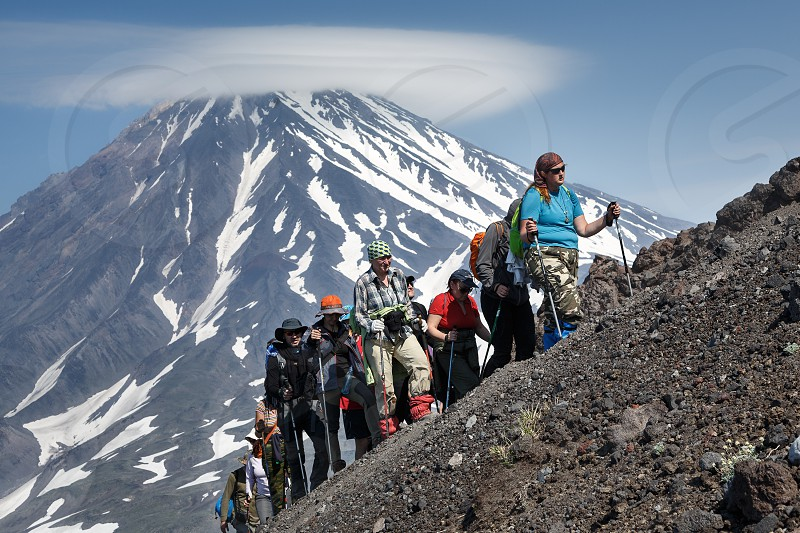 AVACHA VOLCANO KAMCHATKA PENINSULA RUSSIAN FAR EAST - JULY 08 2014: Hiking on Kamchatka - a group of tourists go hiking and climbing to the top of Avachinsky Volcano on background of Koryaksky Volcano. photo