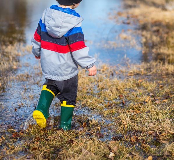 Little boy walking through puddles in the grass wearing rainboots. photo