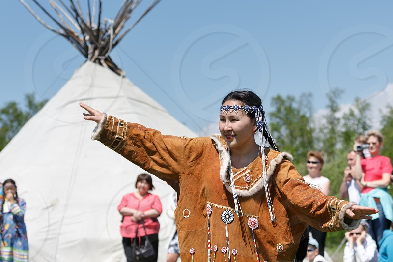 ELIZOVO CITY KAMCHATKA PENINSULA RUSSIA - JUNE 15 2013: Young woman in clothing aborigine of Kamchatka dancing on background of yaranga. Celebration of Day of the first fish - ritual celebration aborigine of Kamchatka. photo
