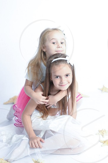 girl with yellow long hair in white shirt and pink lace skirt hugging girl in white tube and lace skirt on her back with white background photo