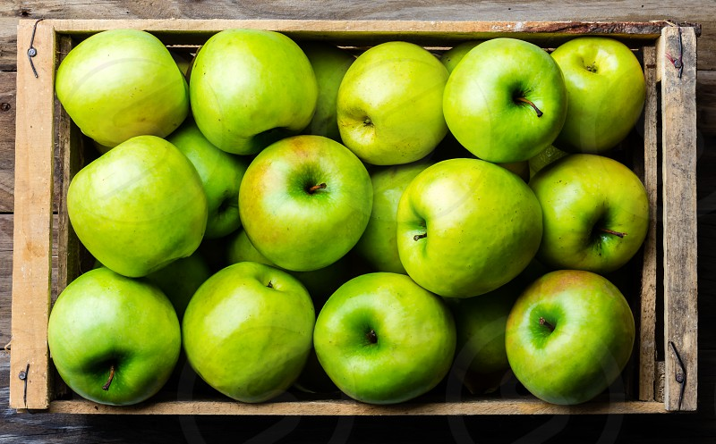 Box of fresh green apples on wooden background. Harvest concept. Top view photo