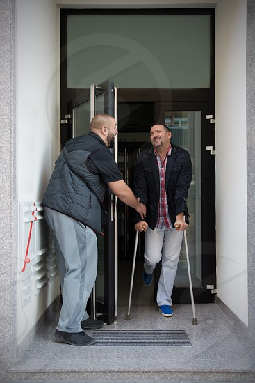 Strong young man helping man on crutches to exit the double door photo