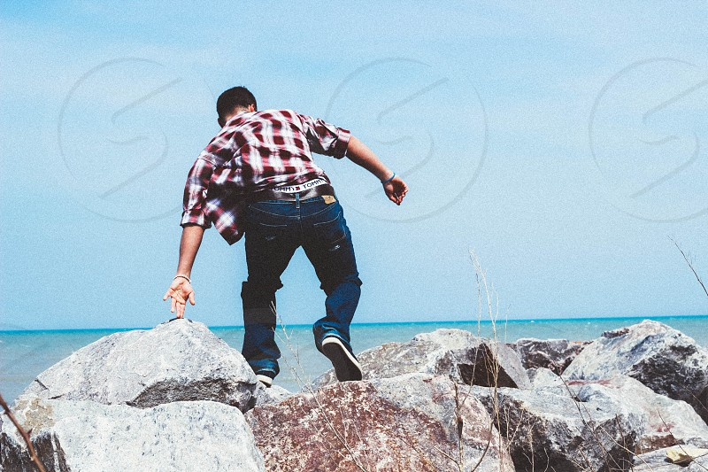 man wearing red checked print button down shirt and blue denim jeans standing on the rock photo